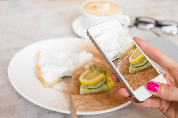 Woman taking food photo in cafe with mobile phone
